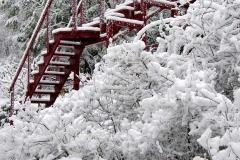 Passerelle rouge carmin sous la neige